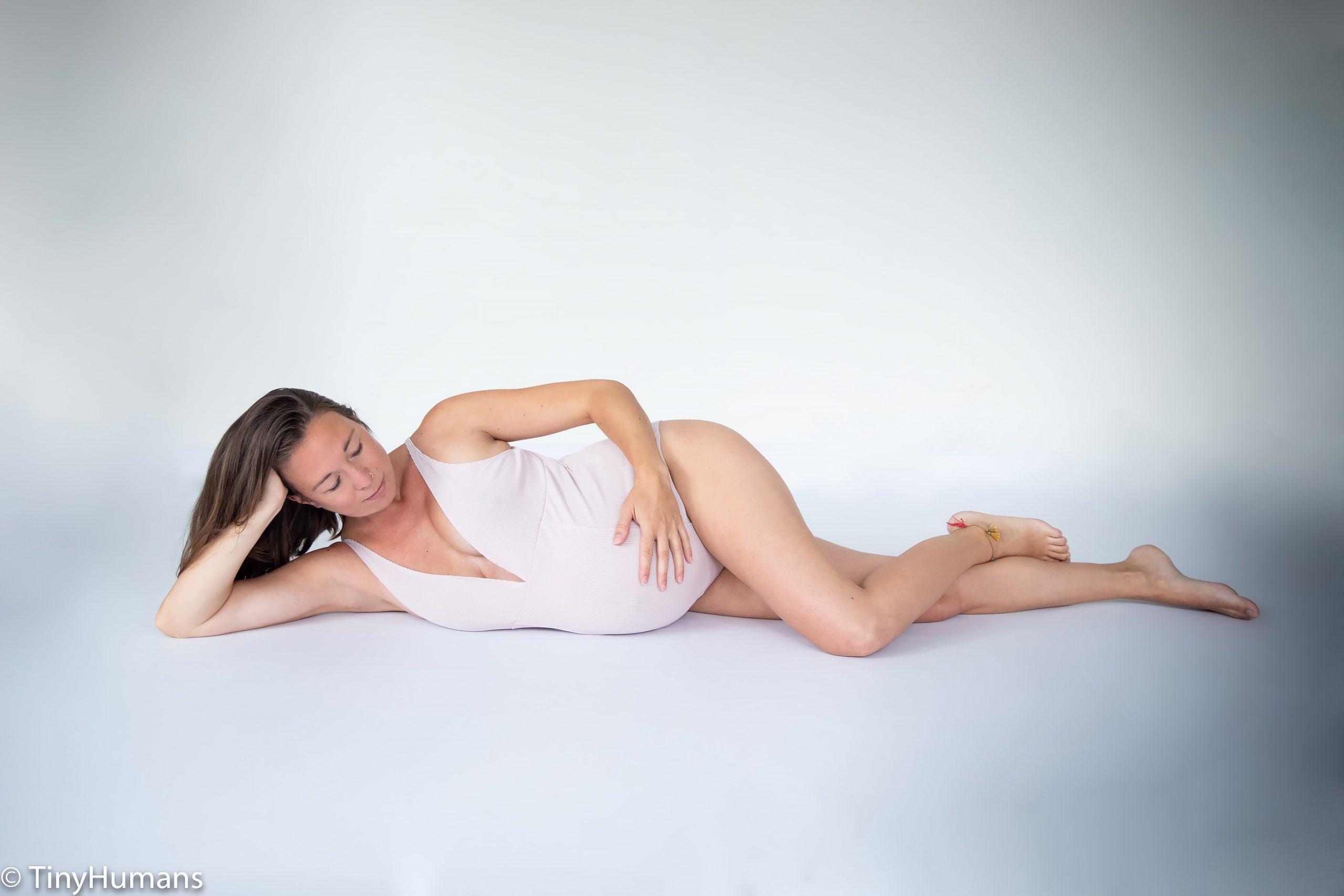 Pregnant woman loving her tummy at pregnancy photo shoot