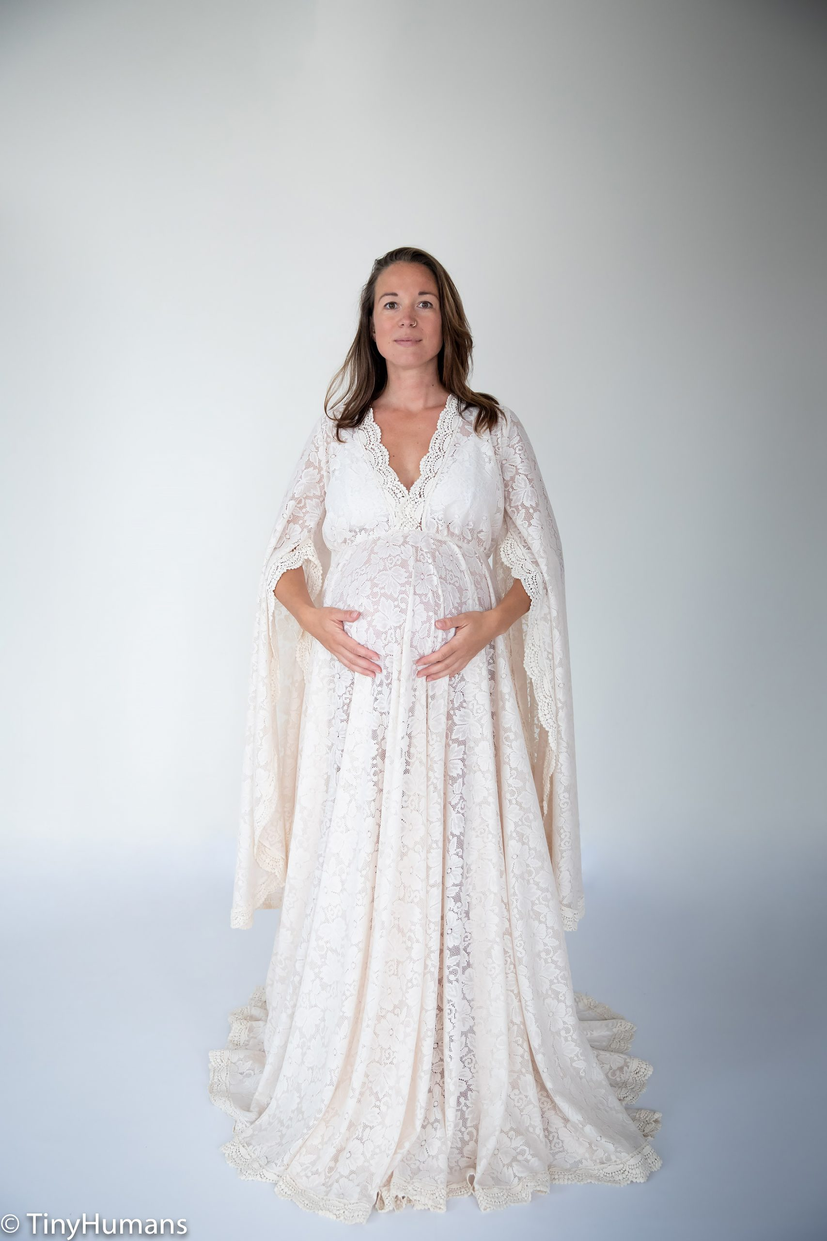 Pregnant  woman with white dress just like a duchess at her pregnancy photo shoot
