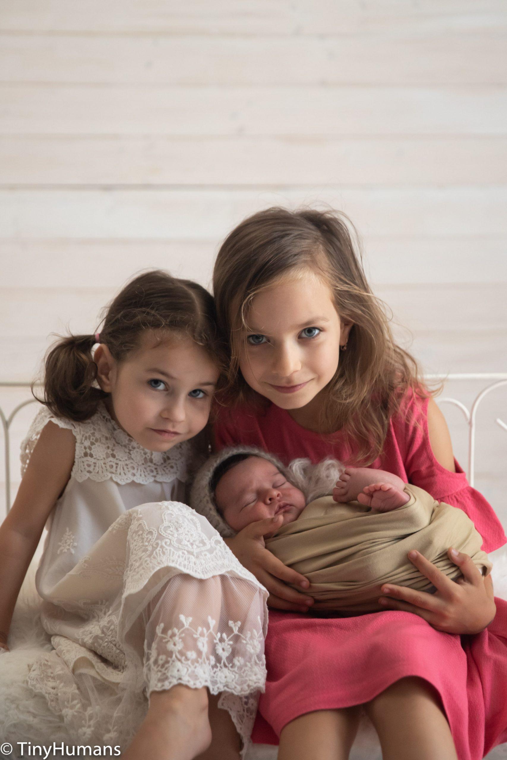 Sleeping newborn with his siblings
