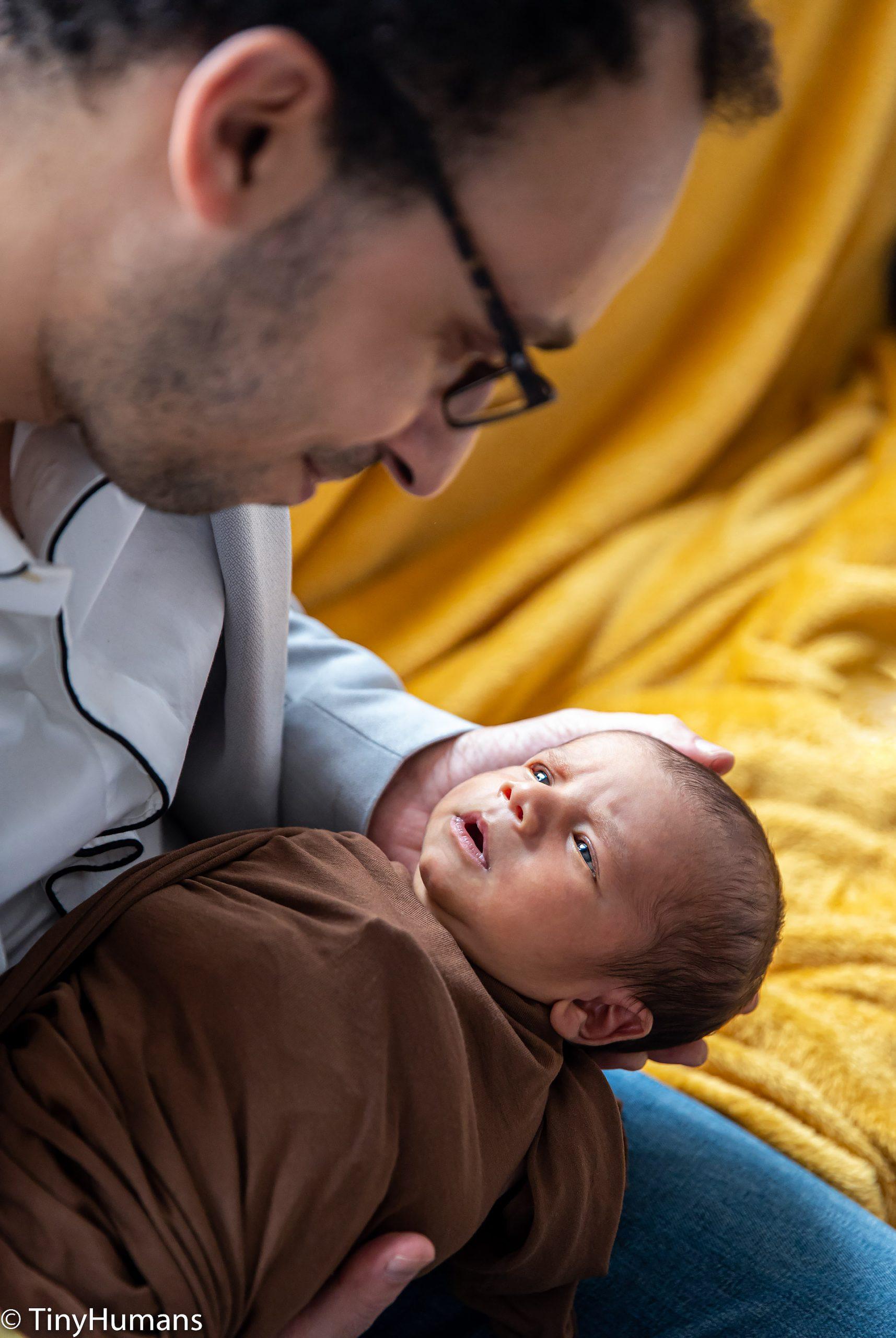 Daddy cuddles newborn