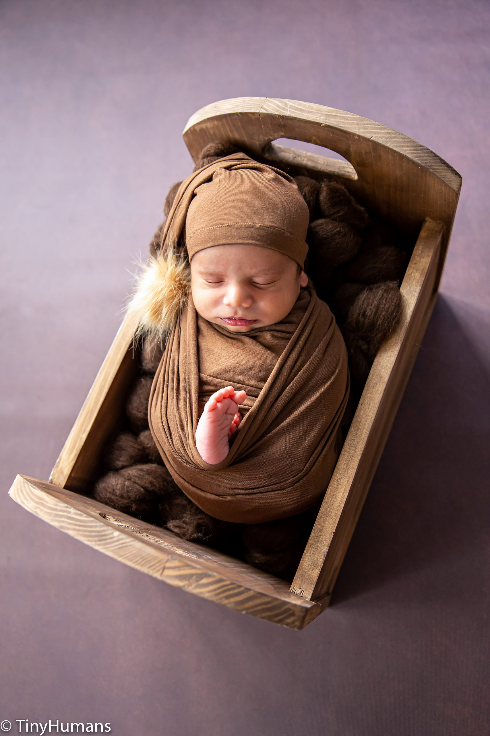 Newborn baby on brown wrap and backdrop