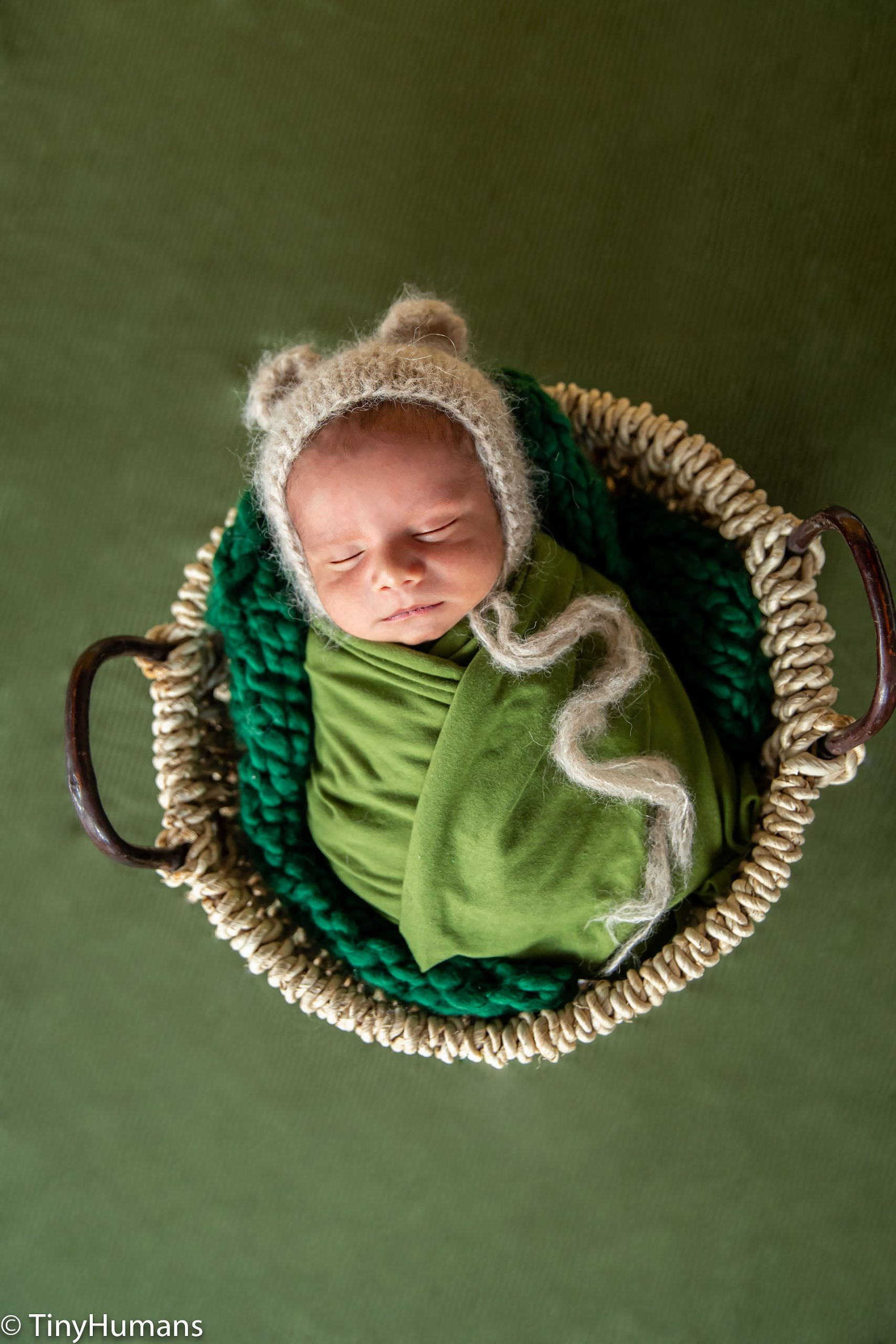 Newborn baby on green wrap and backdrop